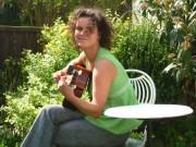 Julia mit Gitarre auf dem Rasen