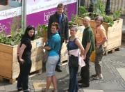 Sechs Mitglieder der Essbaren Stadt vor Pflanzkästen
