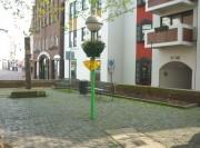 Links der Pranger, im  Hintergrund eine Häuserfront