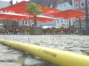 Der Wasserschlauch auf dem  Pflaster des Marktes